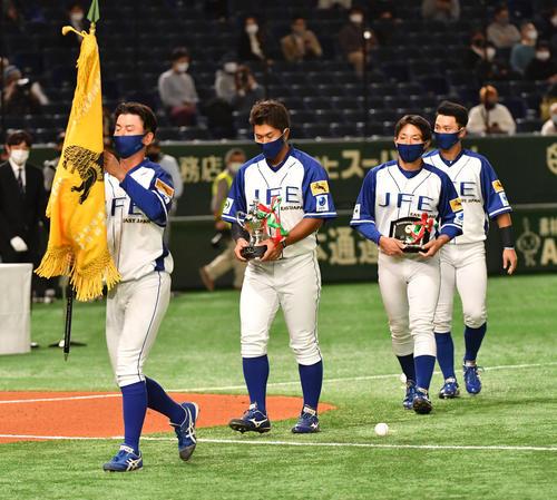JFE東日本対三菱自動車倉敷オーシャンズ 試合前の開会式で前年度優勝のJFE東日本ナインは優勝のレプリカを持ち引き揚げる(撮影・柴田隆二)