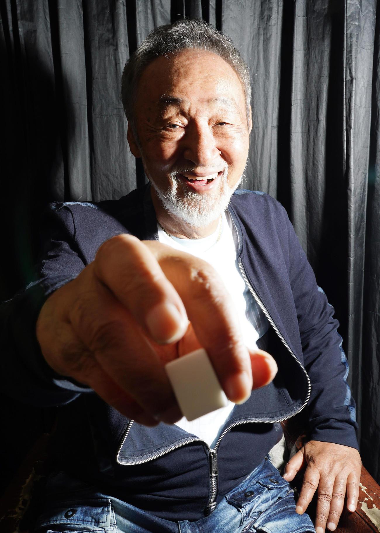牌を手に笑顔を見せる雀士の桜井章一氏