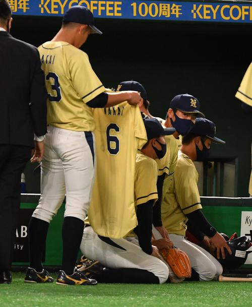 東芝対NTT西日本 試合後、4月に急逝したNTT西日本・中井諒遊撃手のユニホームを持ち勝利を分かち合った(撮影・柴田隆二)