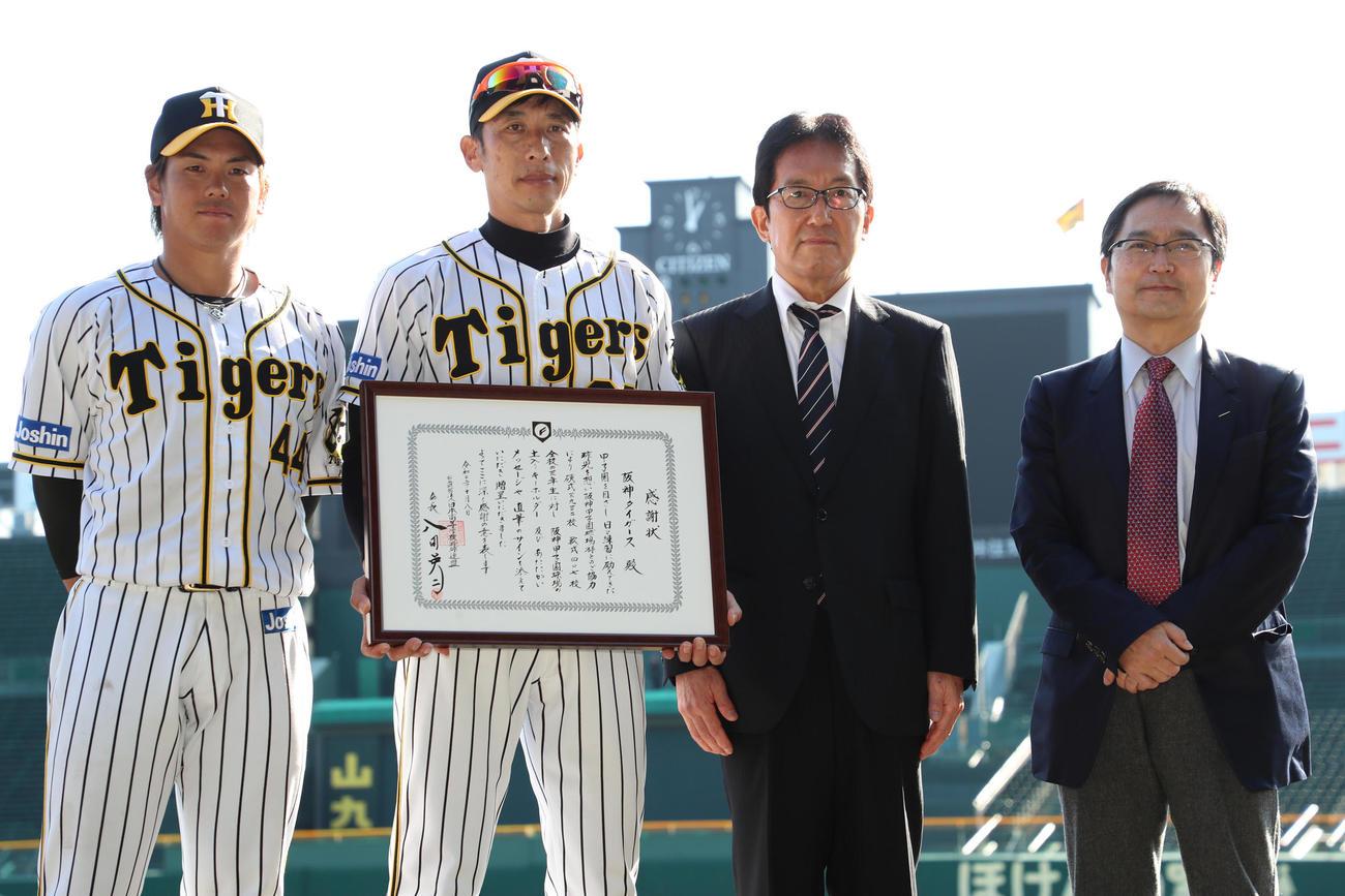 日本高野連から感謝状を受け取る矢野監督(左から2人目)、左から梅野、1人おいて日本高野連の井上副会長、氏家副会長(撮影・清水貴仁)