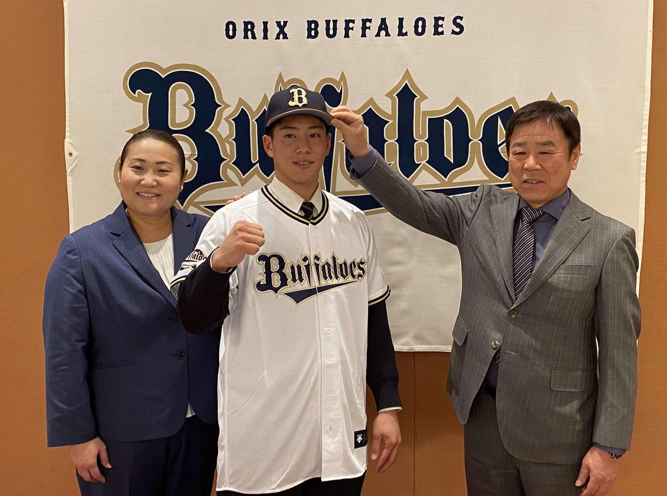 オリックスと仮契約を結んだ明石商・来田涼斗は福良GM(右)に帽子をかぶせてもらいガッツポーズ。左は乾スカウト(撮影・真柴健)