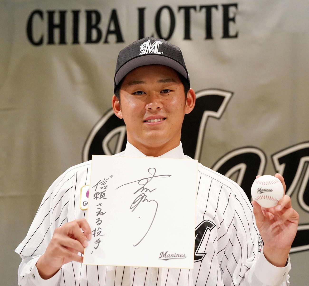 ロッテと仮契約を結んだドラフト1位の法大・鈴木は色紙にサインと「信頼される投手」と記した(撮影・江口和貴)