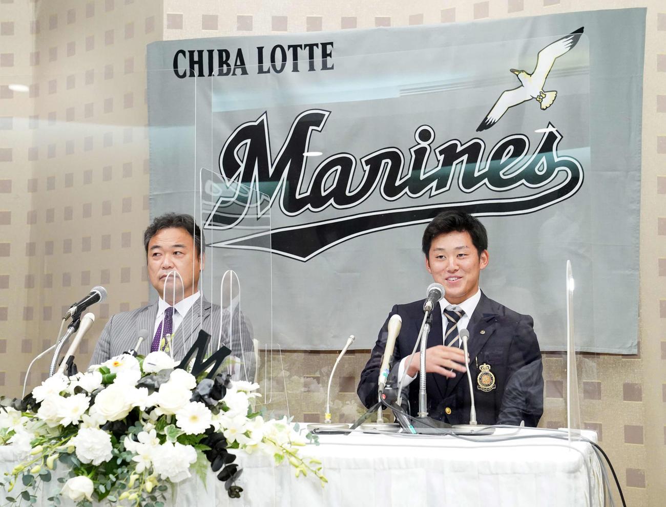 ロッテと仮契約を結び、会見を行うドラフト1位の法大・鈴木(右)。左は永野スカウト部長(撮影・江口和貴)