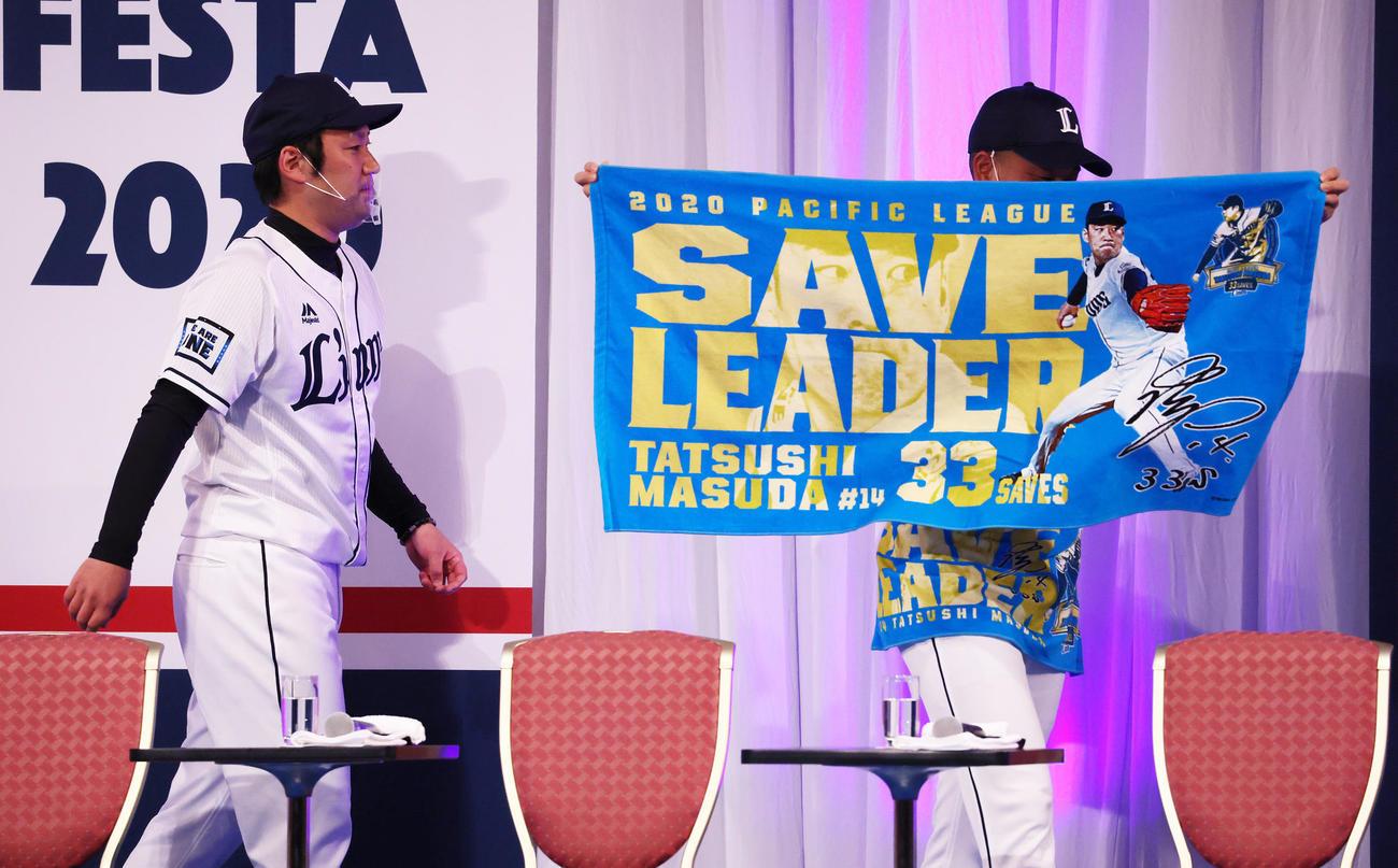 西武増田(左)のセーブ王記念タオルを掲げながら舞台裏へと引き揚げる宮川(撮影・足立雅史)