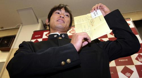08年11月、ドラフトの指名用紙と真弓監督のサインを手に笑顔を見せる早大・上本