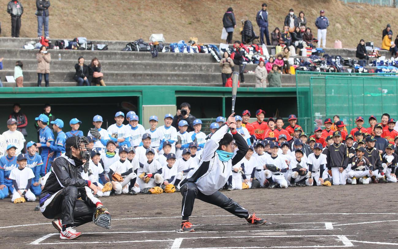 14年12月、大勢の子どもたちが注目する中、兄博紀の打撃フォームをまねて笑いを誘う広島上本