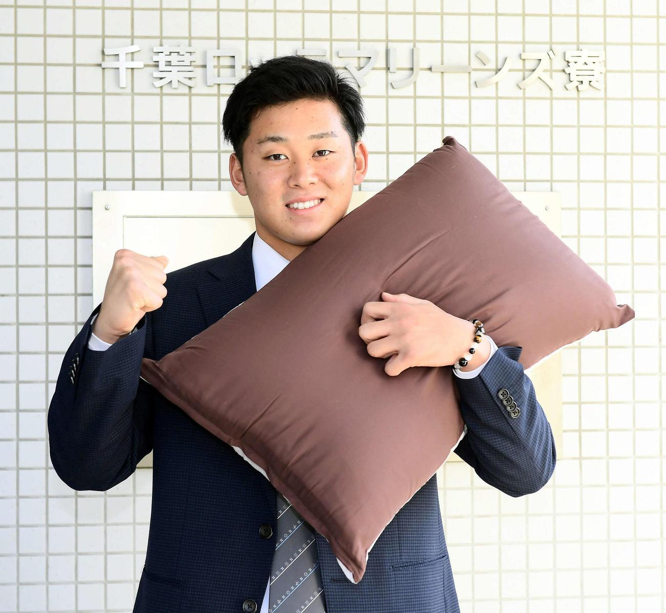持参した枕を手にするドラフト1位の鈴木(代表撮影)