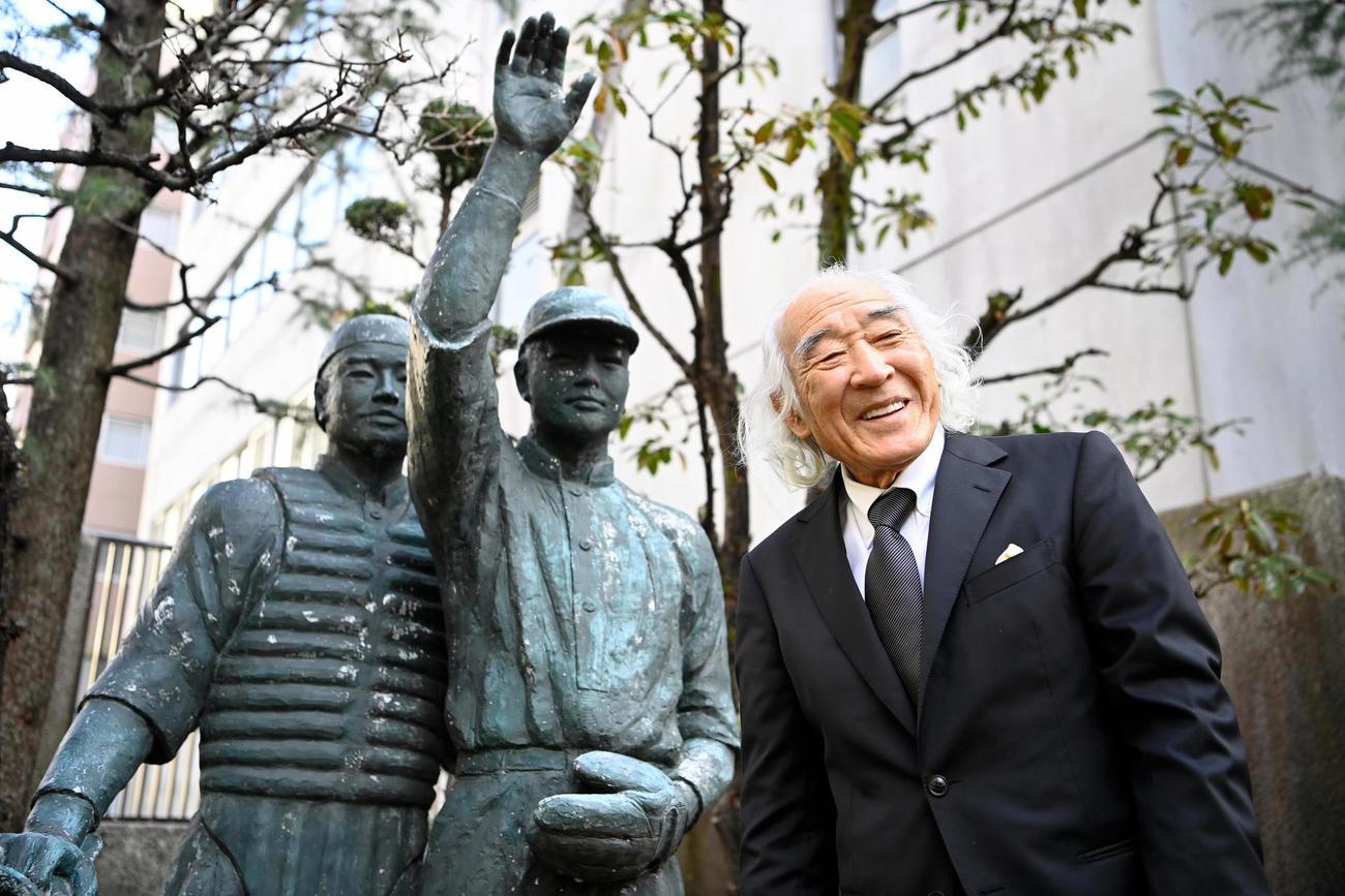 野球殿堂入りし、日本高野連の庭にある銅像の前で笑顔を見せる佐山和夫さん(代表撮影)