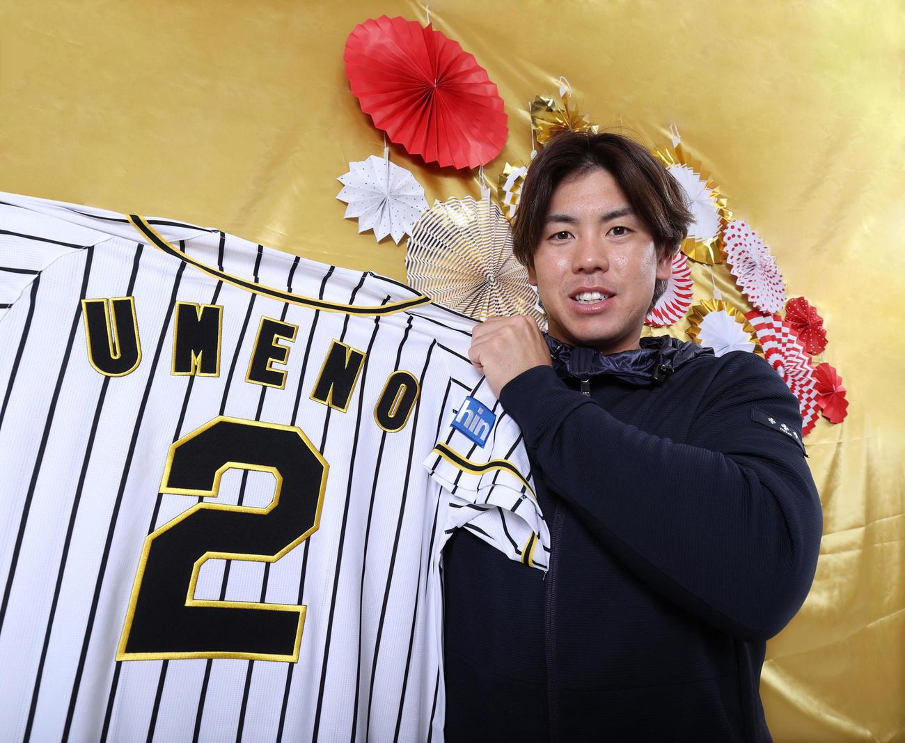 新背番号2のユニホームを手に笑顔をみせる梅野隆太郎(2020年12月19日撮影)