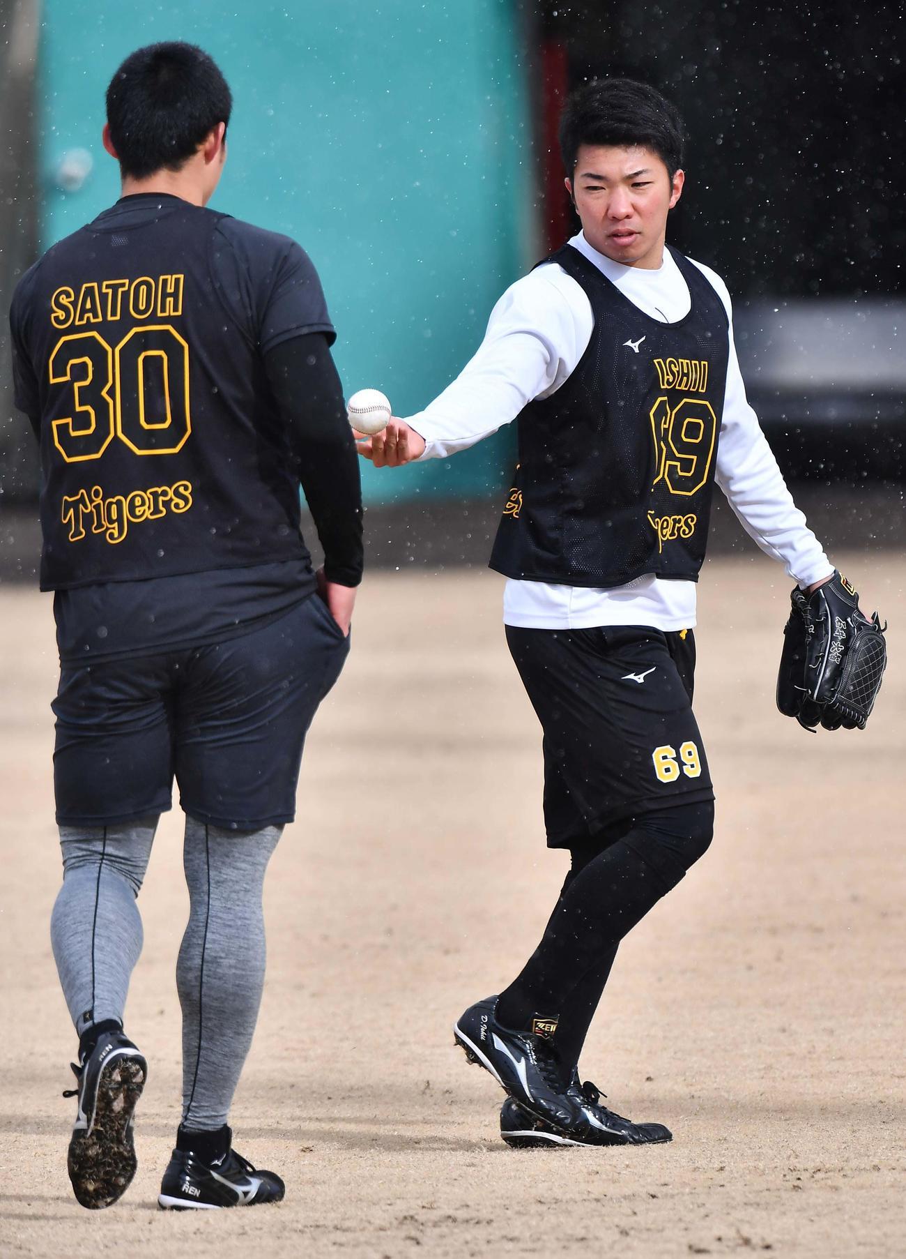 阪神佐藤蓮(左)にボールを渡し先にブルペンに入る石井大智(代表撮影)