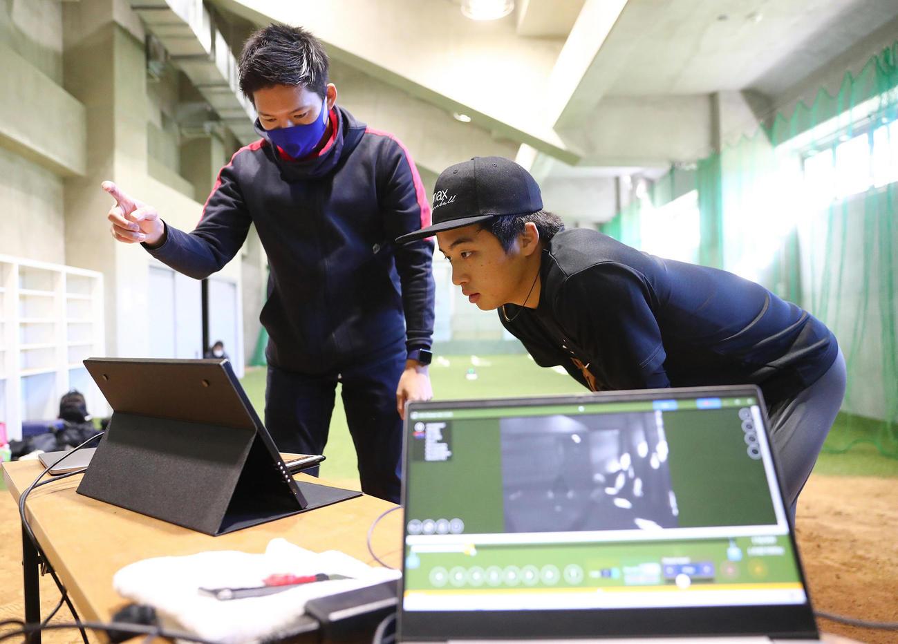 撮影したデータを見てネクストベースの森本氏(左)のアドバイスを受ける中日山本(代表撮影)