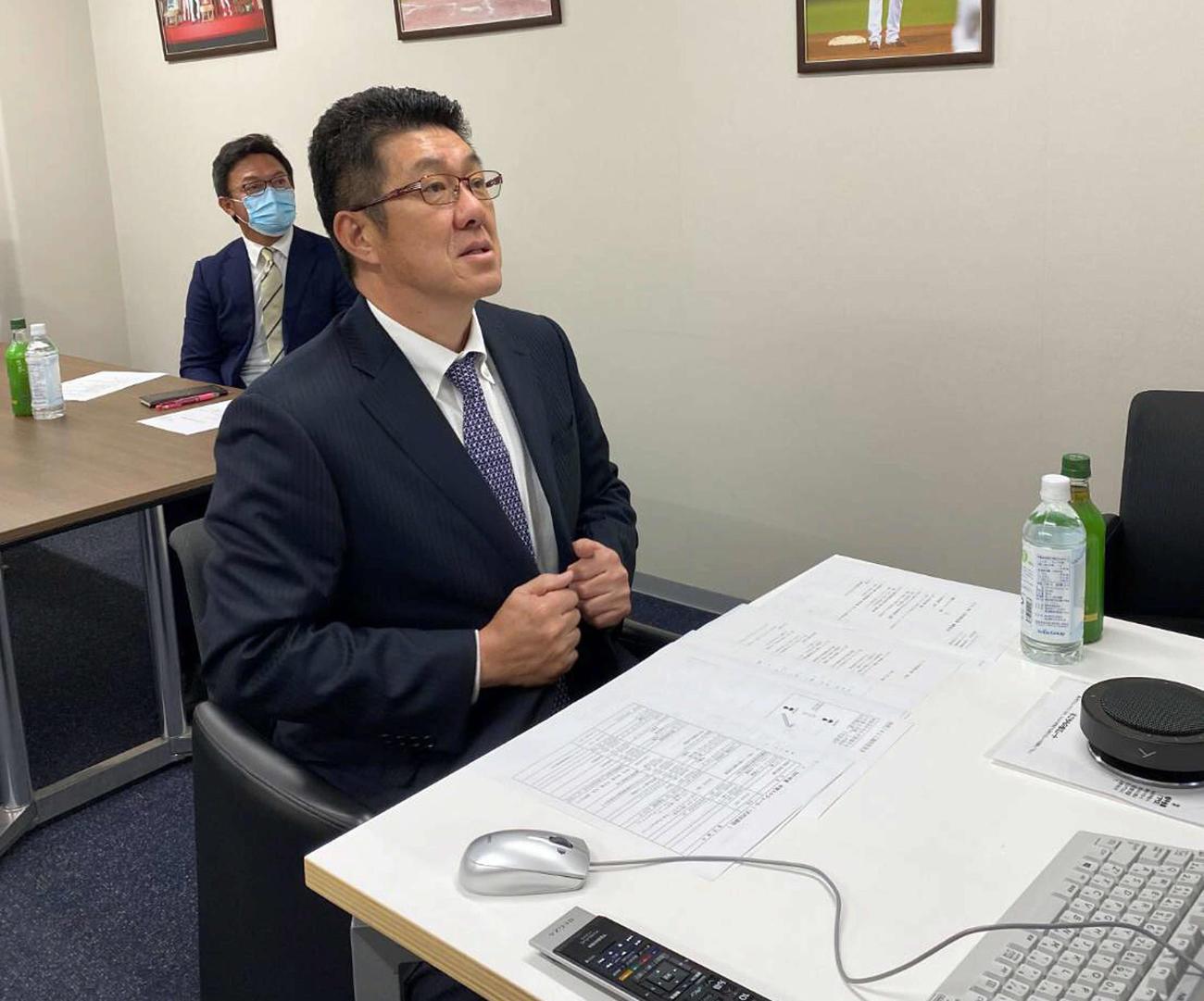 リモートで監督会議に出席した広島佐々岡監督。左は河田ヘッドコーチ(球団提供)
