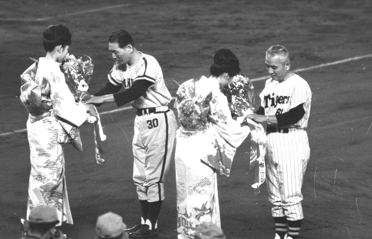 64年、日本シリーズで花束を受け取る南海鶴岡一人監督(左)と、阪神藤本定義監督