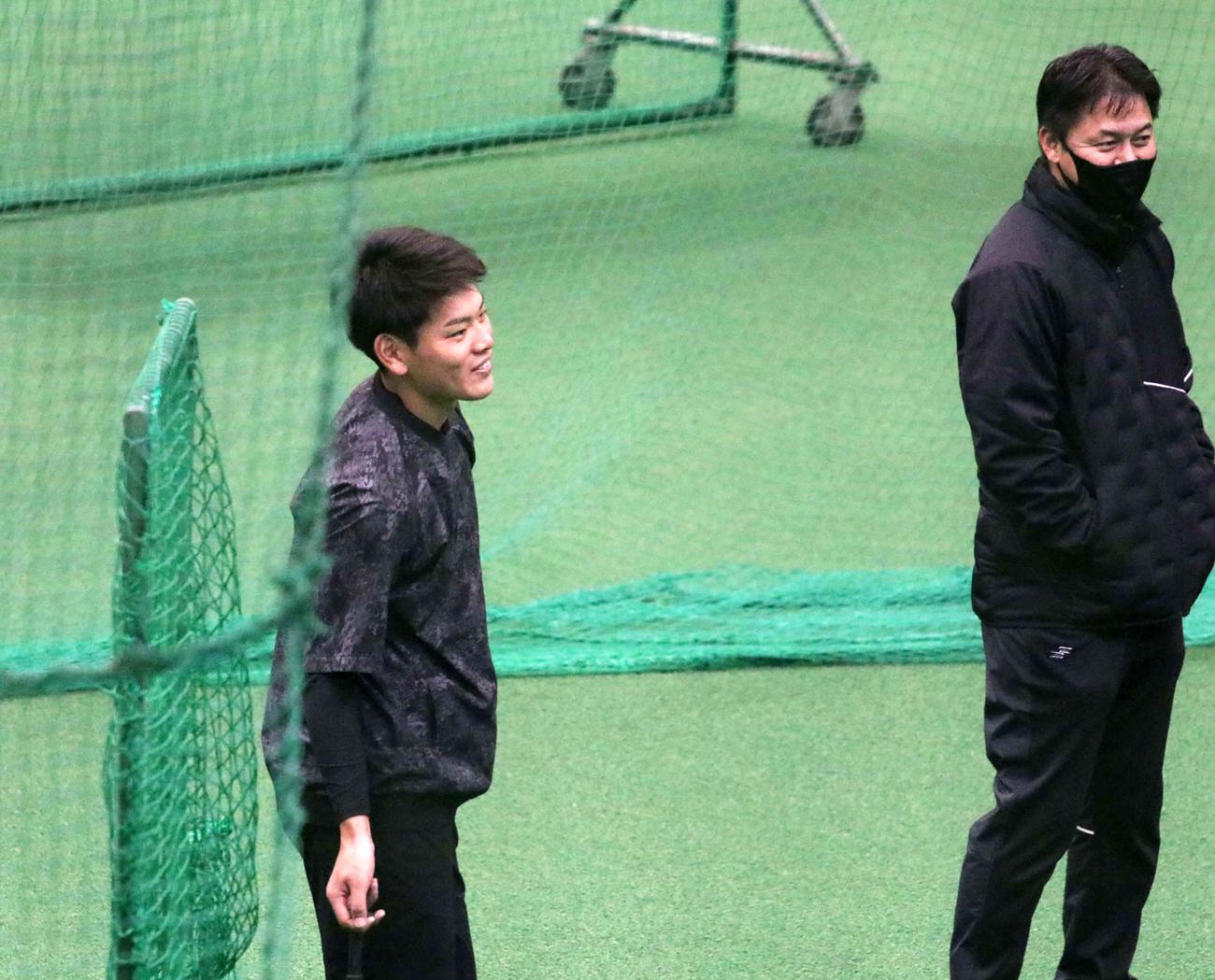 金子誠野手総合コーチ(右)と談笑する日本ハム野村(撮影・山崎純一)