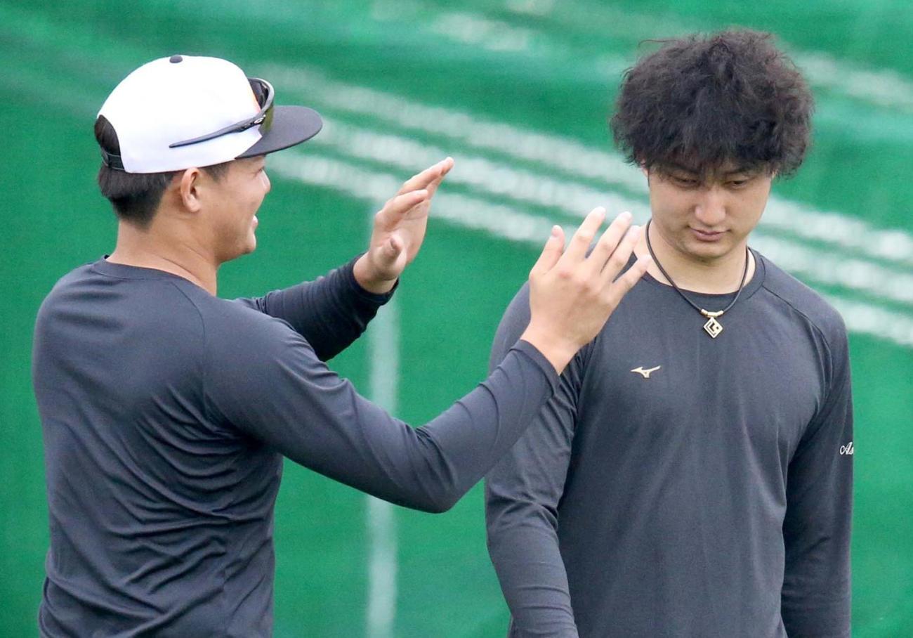 ツイストスパイラルパーマにした日本ハム浅間(右)の髪形に興味を示す郡(撮影・佐藤翔太)