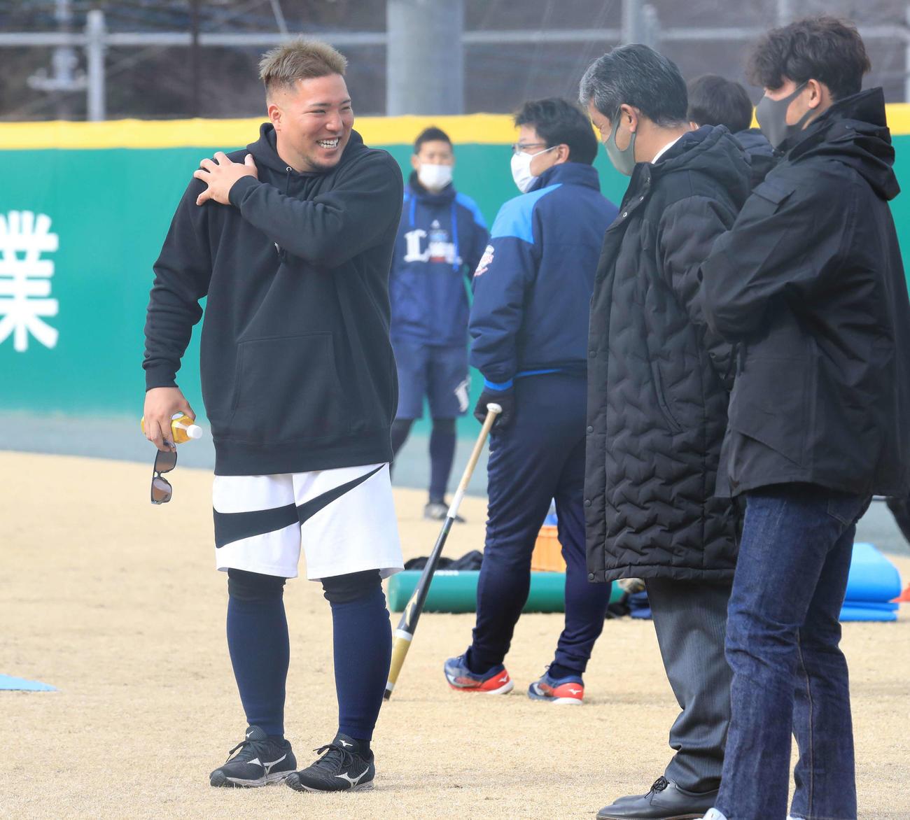 自主トレに訪れた西武山川(左)は球団スタッフと談笑(代表撮影)