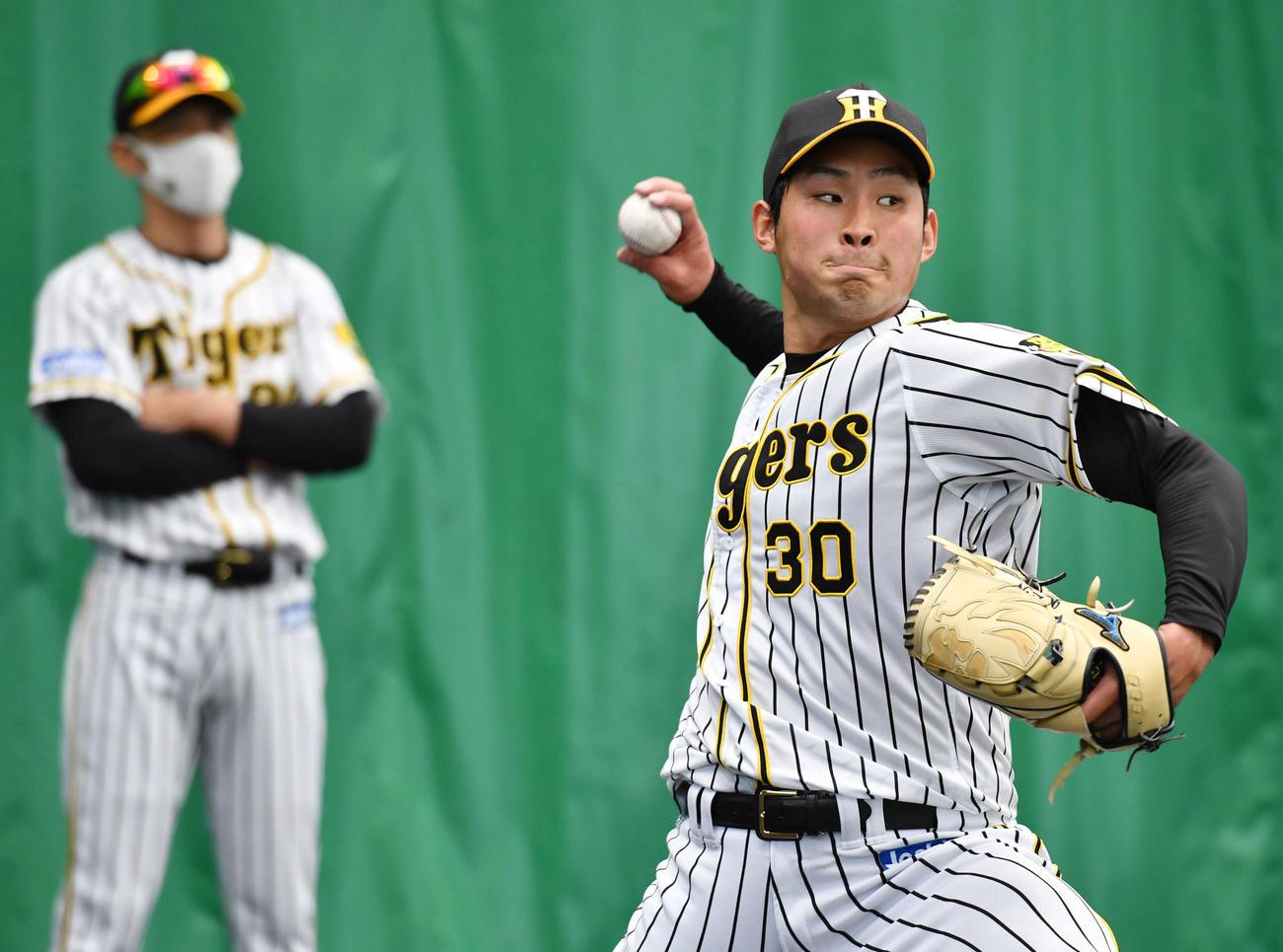 ブルペンで投球する阪神佐藤蓮。左は見つめる矢野監督(代表撮影)