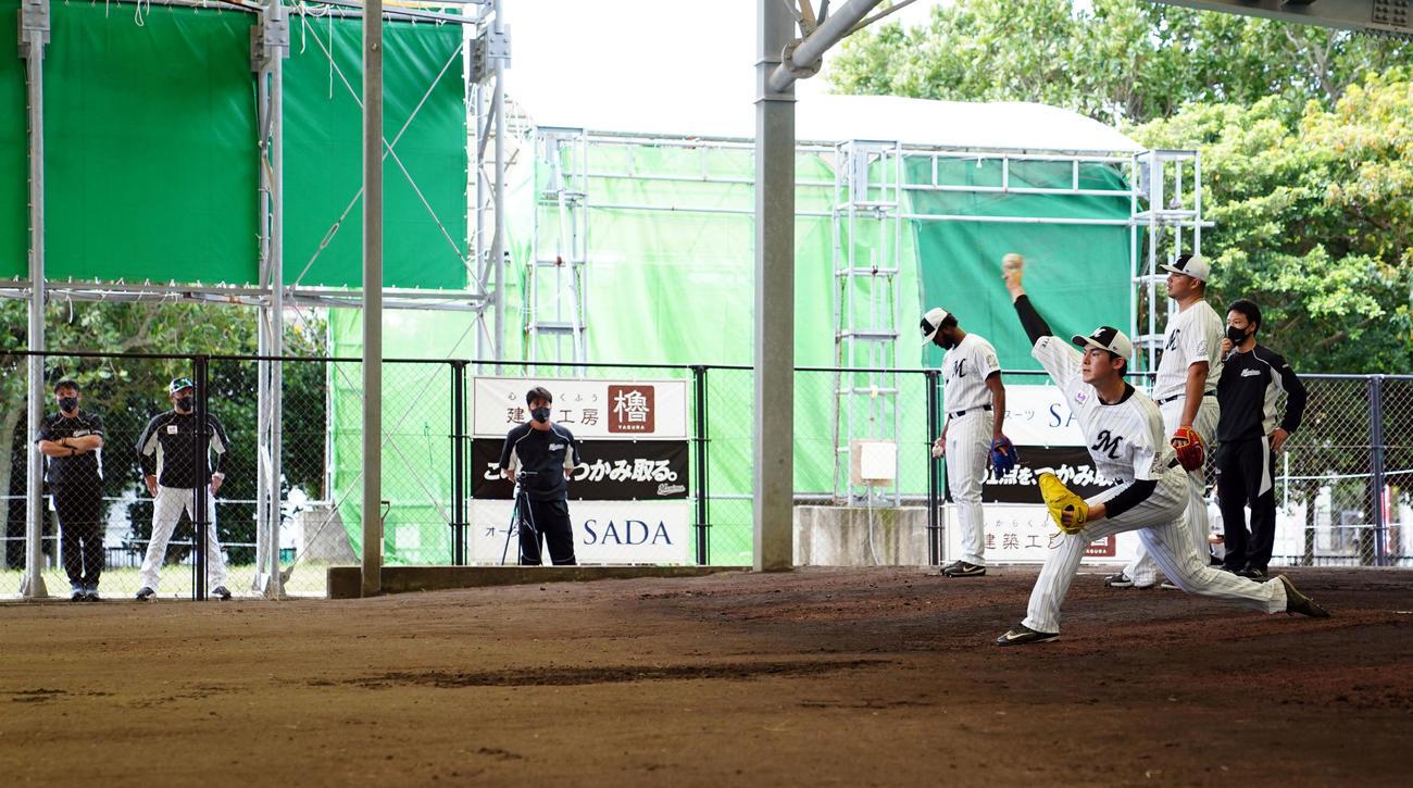 井口監督(左から2人目)が見つめる中ブルペンで投球練習するロッテ佐々木朗(手前)