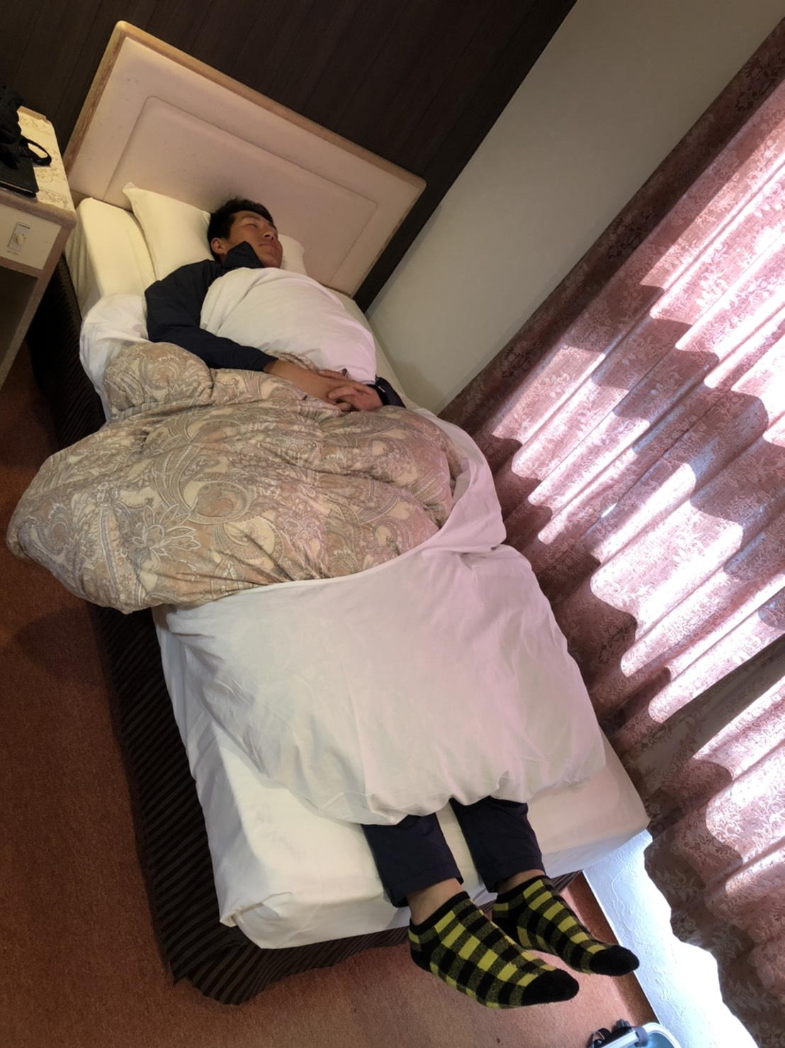 宿舎のベッドに寝る秋広(球団提供)