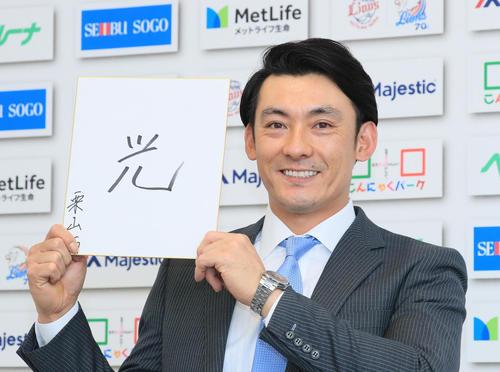 今年の漢字を「光」と記し、笑顔を見せる西武栗山(20年12月代表撮影)