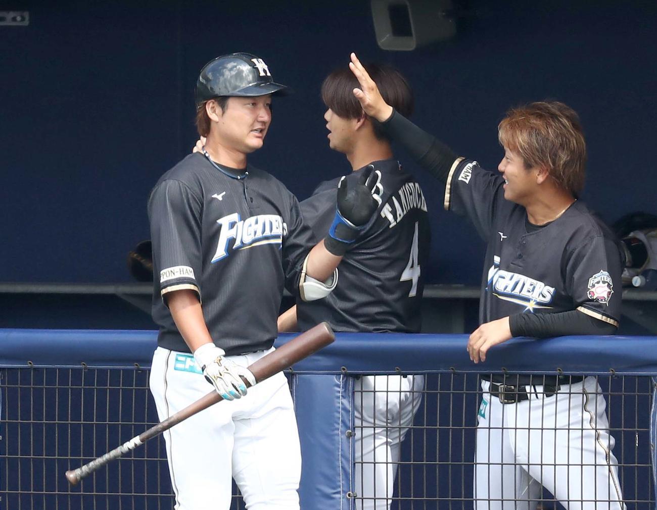 日本ハム紅白戦 3回表2死一、二塁、右中間に3点本塁打を放ち出迎えられる渡辺(撮影・黒川智章)