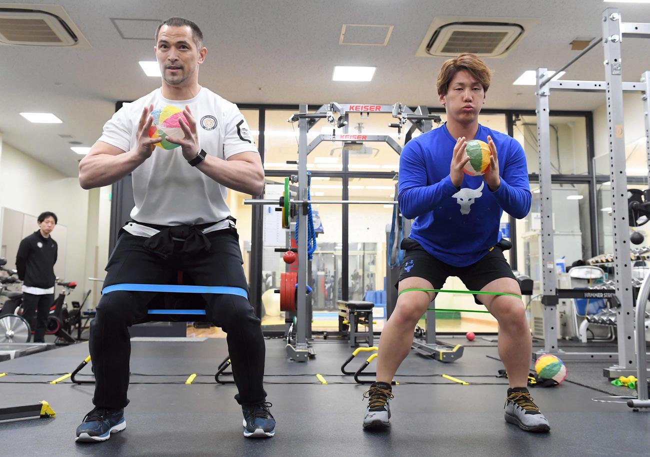19年1月、室伏広治氏(左)の指導を受け紙風船を使ってトレーニングするオリックス吉田正