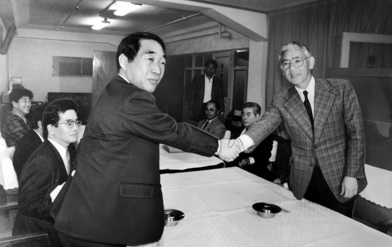 会議の席で「よろしくお願いします」と握手を交わす鵜木洋二新球団社長(左)とダイエー・杉浦忠監督=1988年10