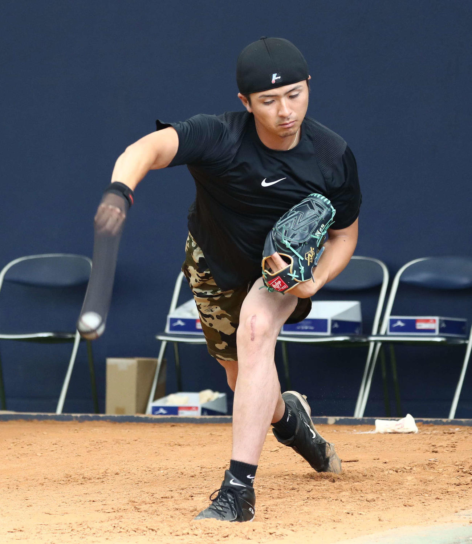 右手に投球用の練習器具を装着してシャドーピッチングする日本ハム上沢(撮影・黒川智章)
