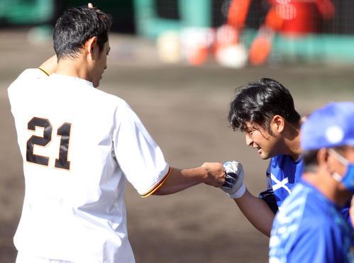 巨人対DeNA 試合前の練習で、嶺井(右)とあいさつを交わす井納(撮影・狩俣裕三)