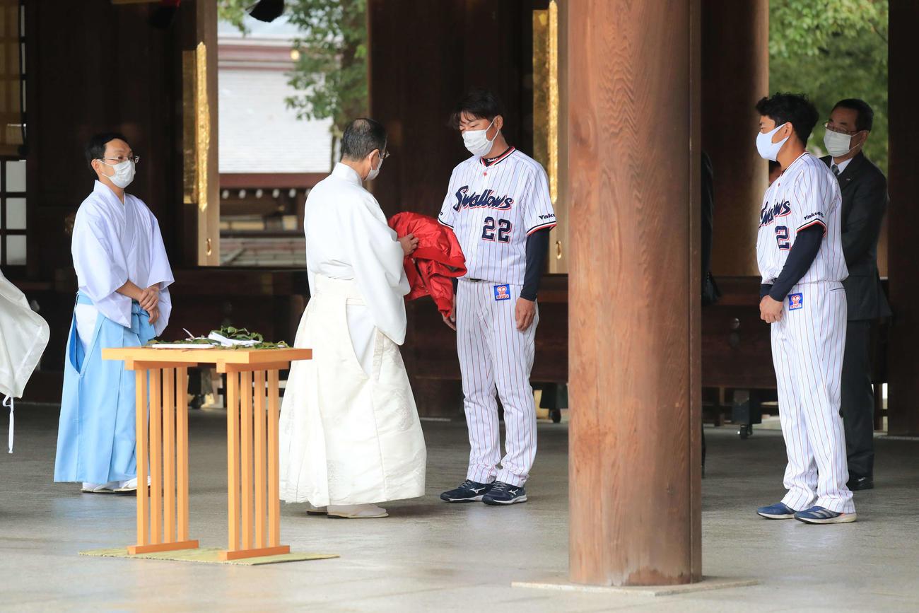 明治神宮を参拝し、宮司の中島精太郎さんから赤色のジャンパーを受け取るヤクルト高津監督