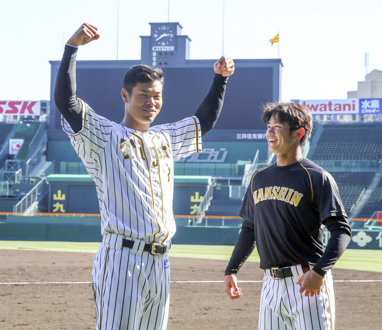 佐藤輝は甲子園球場のスコアボードをバックにポーズを決める、右は中野(撮影・上山淳一)