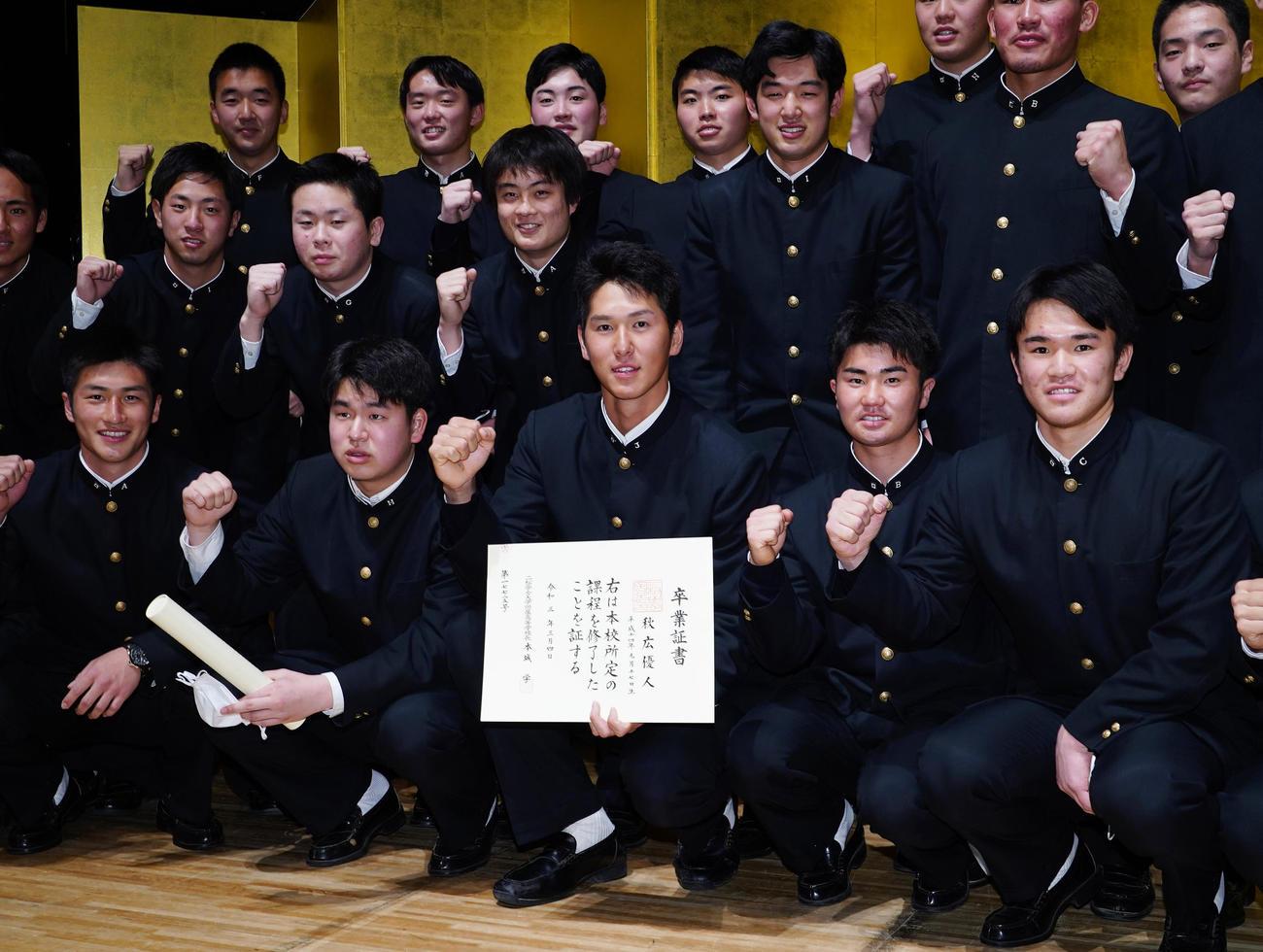 二松学舎大付高の卒業式を終え、チームメートと記念写真に納まる巨人秋広(中央)(撮影・菅敏)