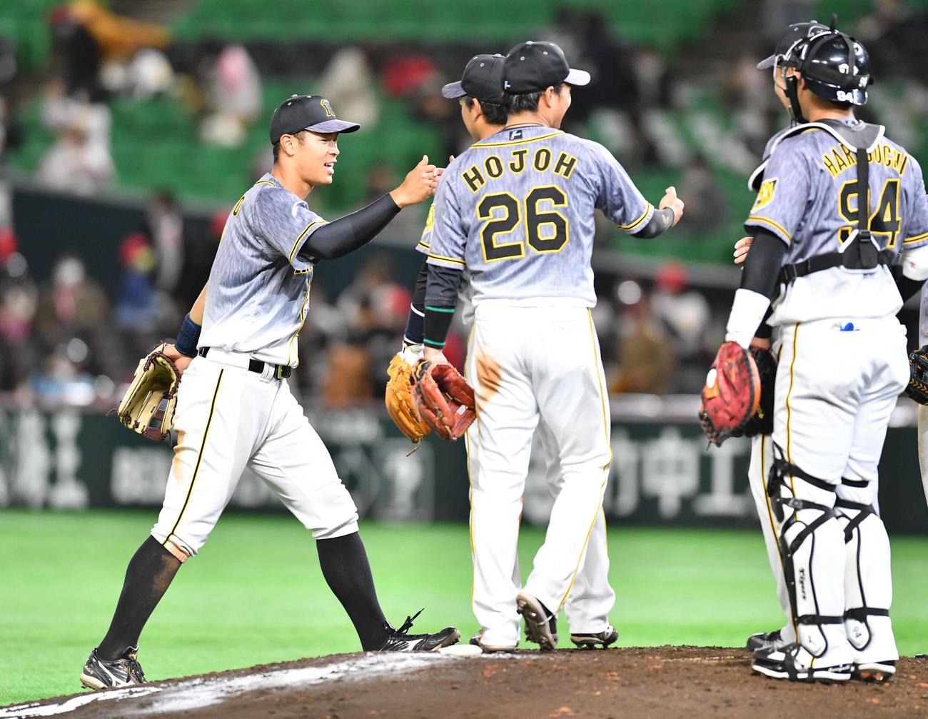 2021年3月5日 ソフトバンク対阪神 ソフトバンクに勝利し、佐藤輝明(左)はナインとグータッチを交わす(撮影・岩下翔太)