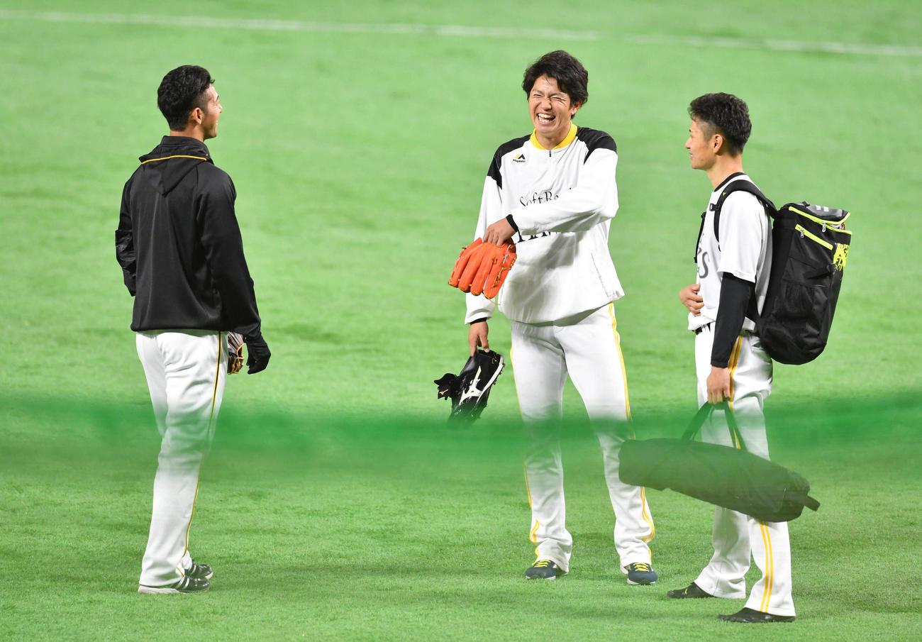 試合前、阪神・加治屋(左)と談笑するソフトバンク高橋礼(中央)と大竹(撮影・岩下翔太)