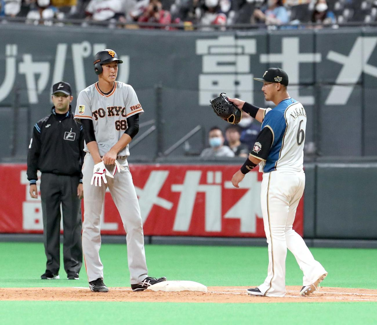 3月6日の日本ハム戦の5回表に、巨人秋広は右前打を放ち日本ハム一塁手の中田と言葉を交わす(撮影・佐藤翔太)