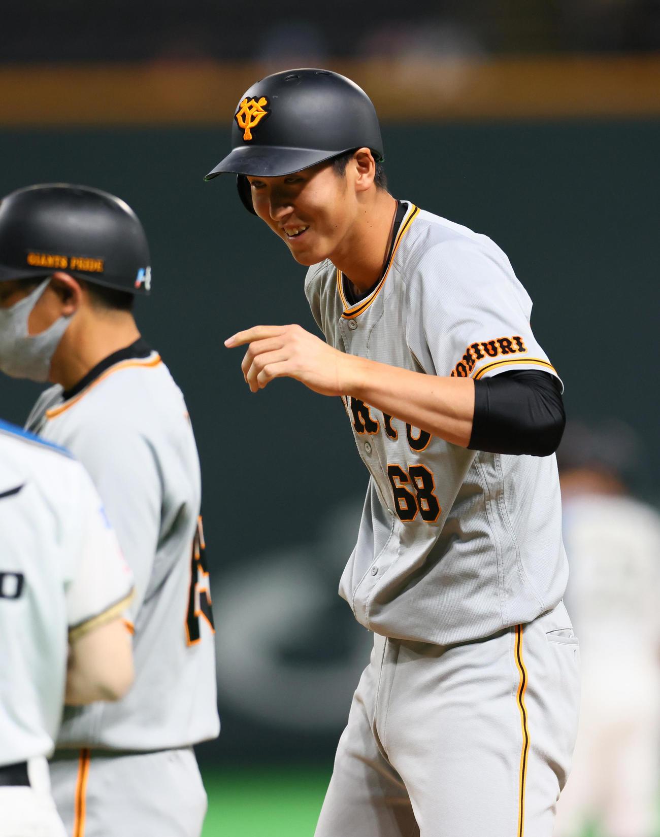 日本ハム対巨人 2回表巨人2死一、二塁、左前打を放ち笑顔を見せる秋広(撮影・足立雅史)