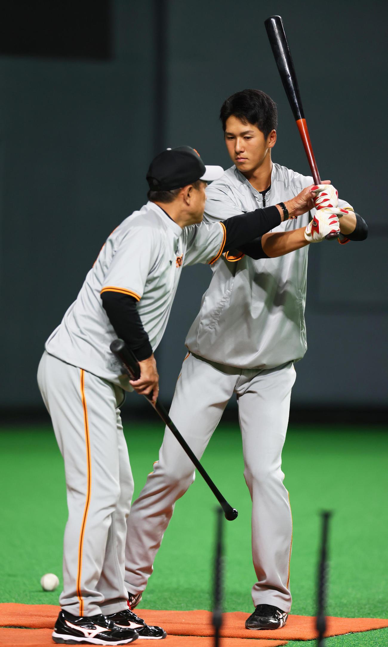 試合前、巨人原監督(左)から打撃指導を受ける秋広(撮影・足立雅史)
