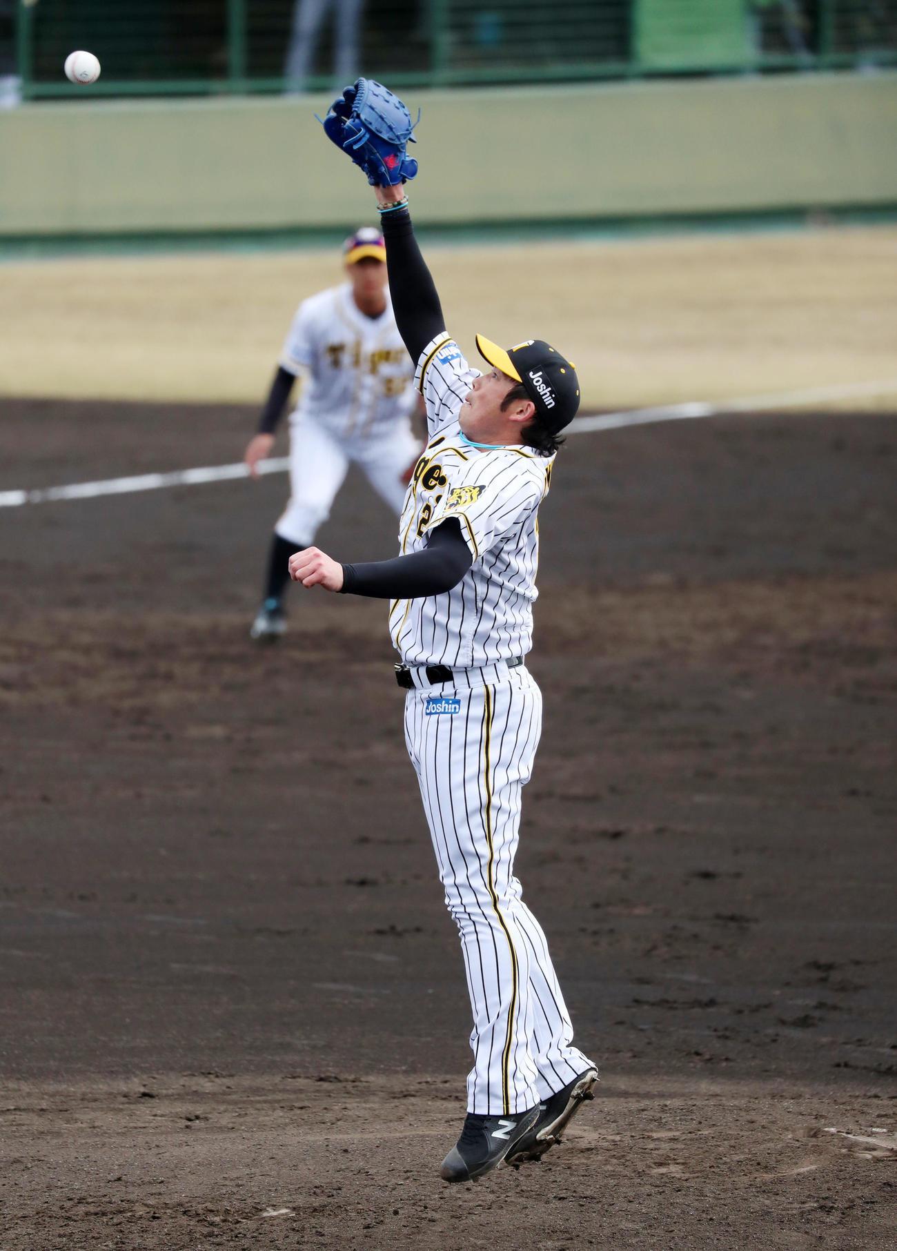 阪神対関大 3回表関大1死一塁、岩田は久保田有の打球をジャンプして捕球する(代表撮影)