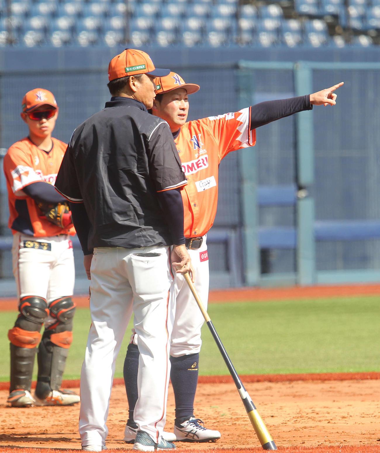 橋上監督(背中)と練習の打ち合わせをする稲葉内野手兼野手コーチ(右)