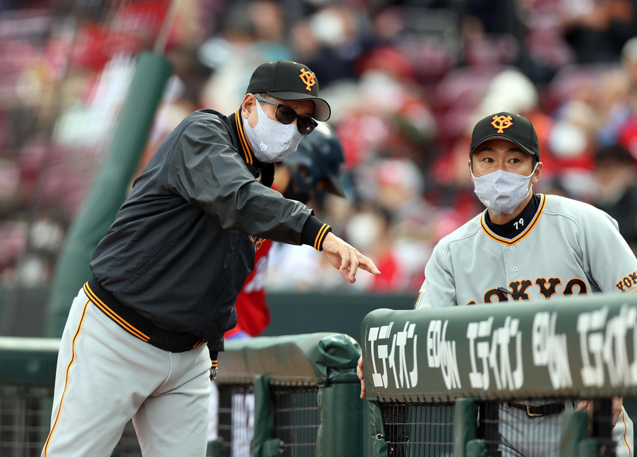 広島対巨人 7回表を終え、相川バッテリーコーチ(右)と話をする原監督(撮影・狩俣裕三)