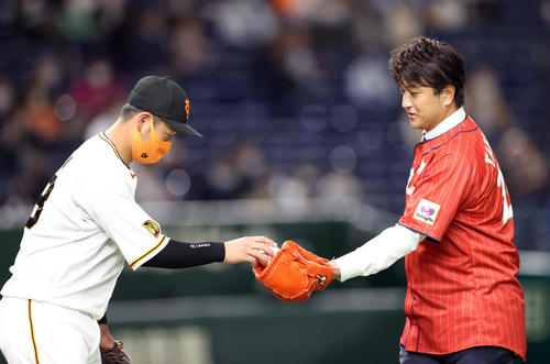 始球式を務め、岸田(左)からボールを受け取る高橋由伸氏(撮影・狩俣裕三)