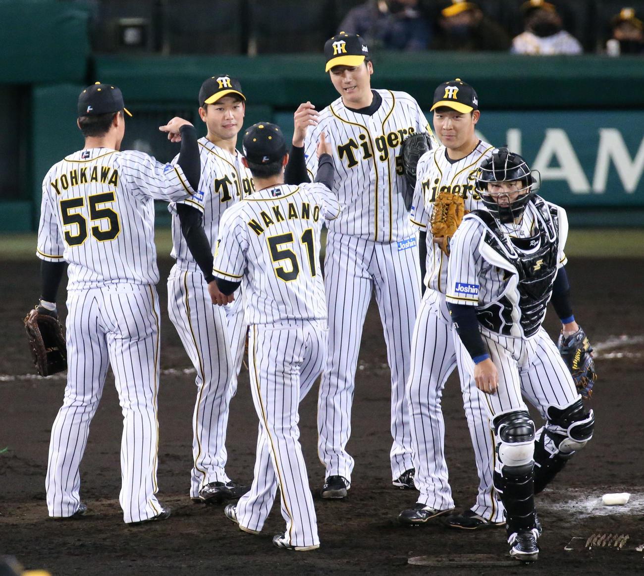阪神対広島 試合を締めた小林(右から3人目)はナインとタッチを交わす(撮影・上山淳一)