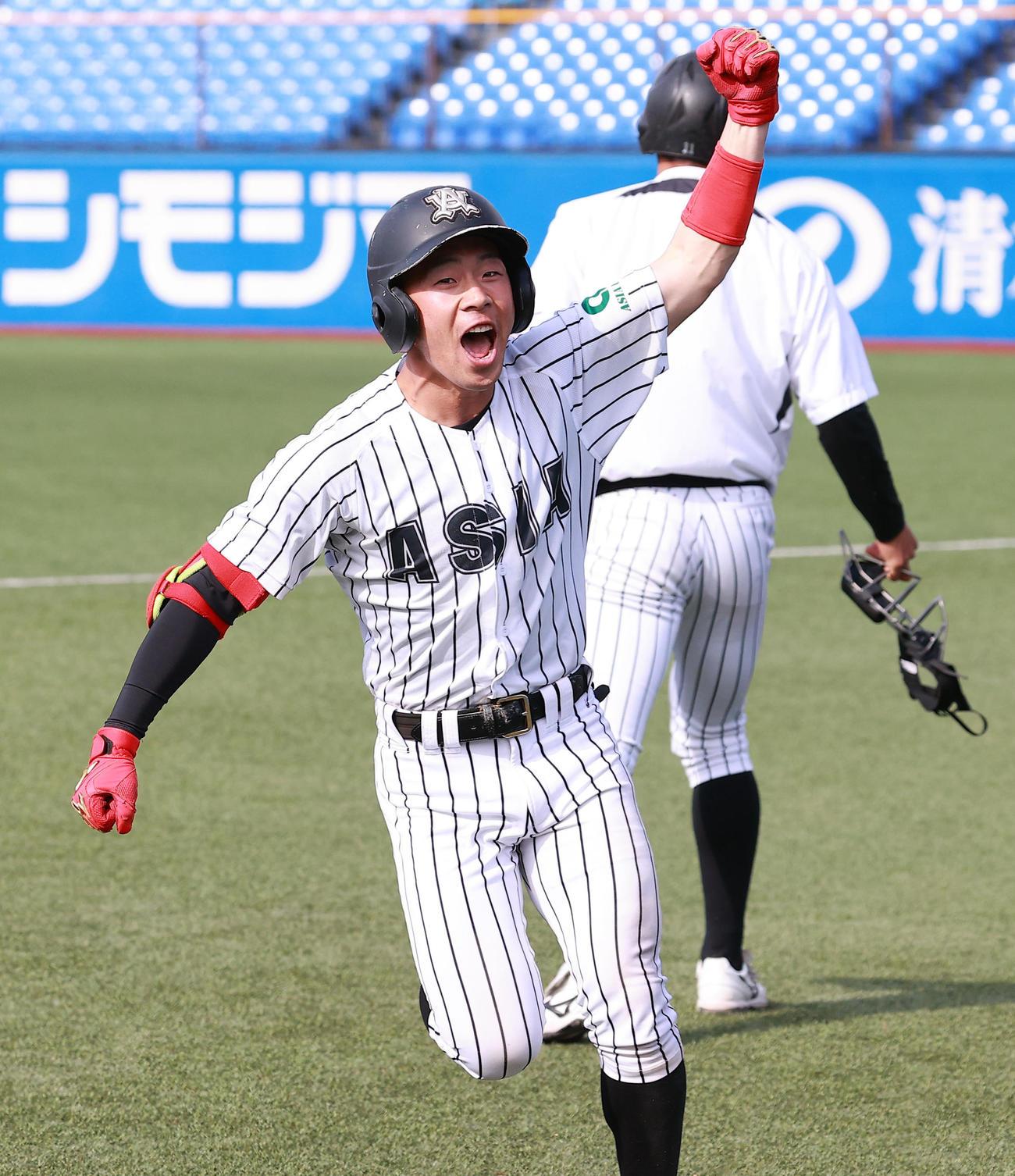 駒大対亜大 10回裏亜大1死満塁、代打後藤はサヨナラスクイズを決め、ガッツポーズでナインのもとに走る(撮影・浅見桂子)