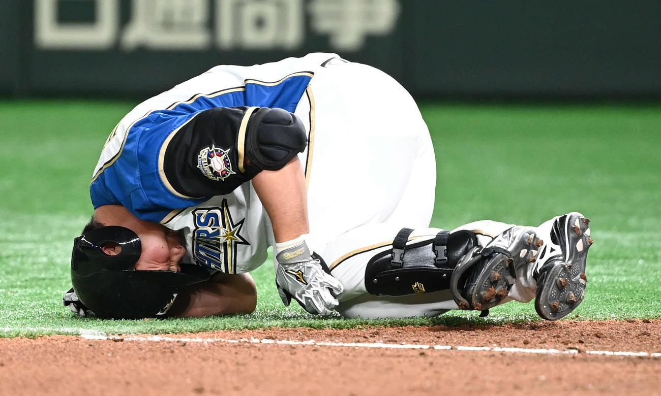 日本ハム対楽天 9回裏日本ハム2死二塁、死球を食らった樋口は倒れ込む(撮影・山崎安昭)