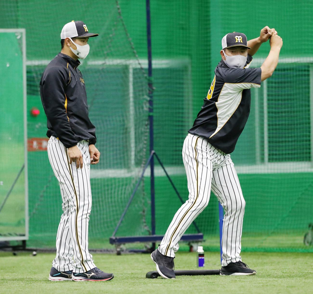 室内で佐藤輝明(左)は井上ヘッドコーチから打撃フォームのアドバイスをうける(2021年4月17日撮影)