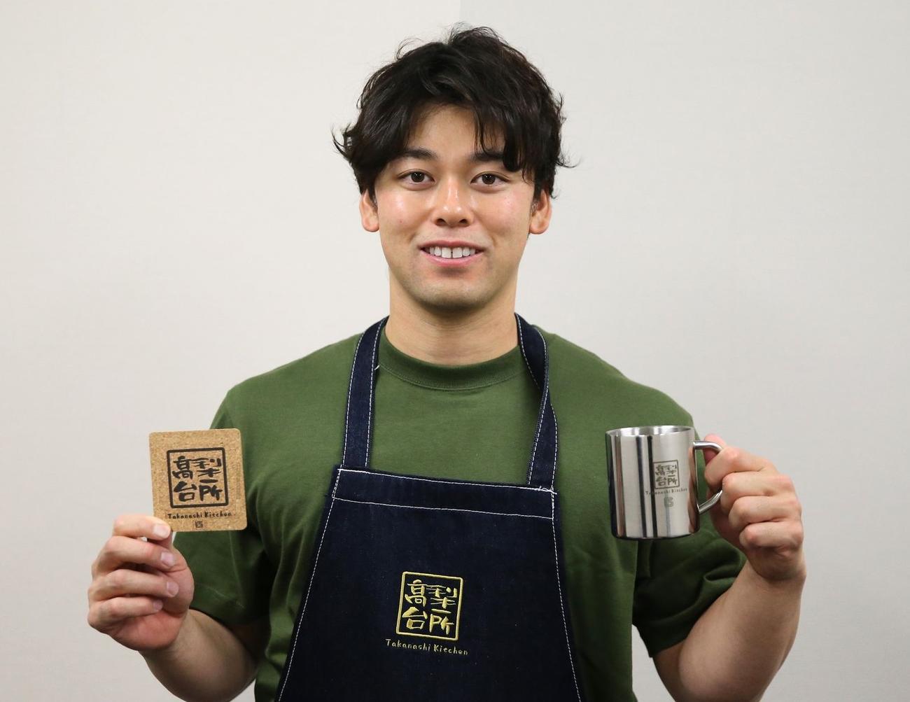 19日から発売された「たかなしきっちん」グッズを手に笑顔の巨人高梨雄平投手(球団提供)