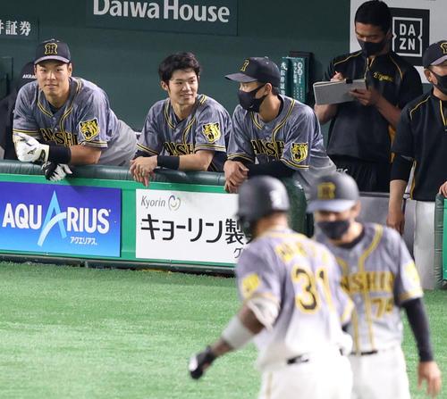 巨人対阪神 3回表阪神無死一塁、2点本塁打を放ったマルテ(手前)をベンチから笑顔で見つめる佐藤輝(後方左)(撮影・狩俣裕三)