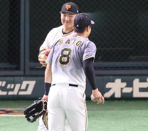 巨人対阪神 試合前、佐藤輝(手前)からあいさつされ、笑顔で応える岡本和(撮影・狩俣裕三)