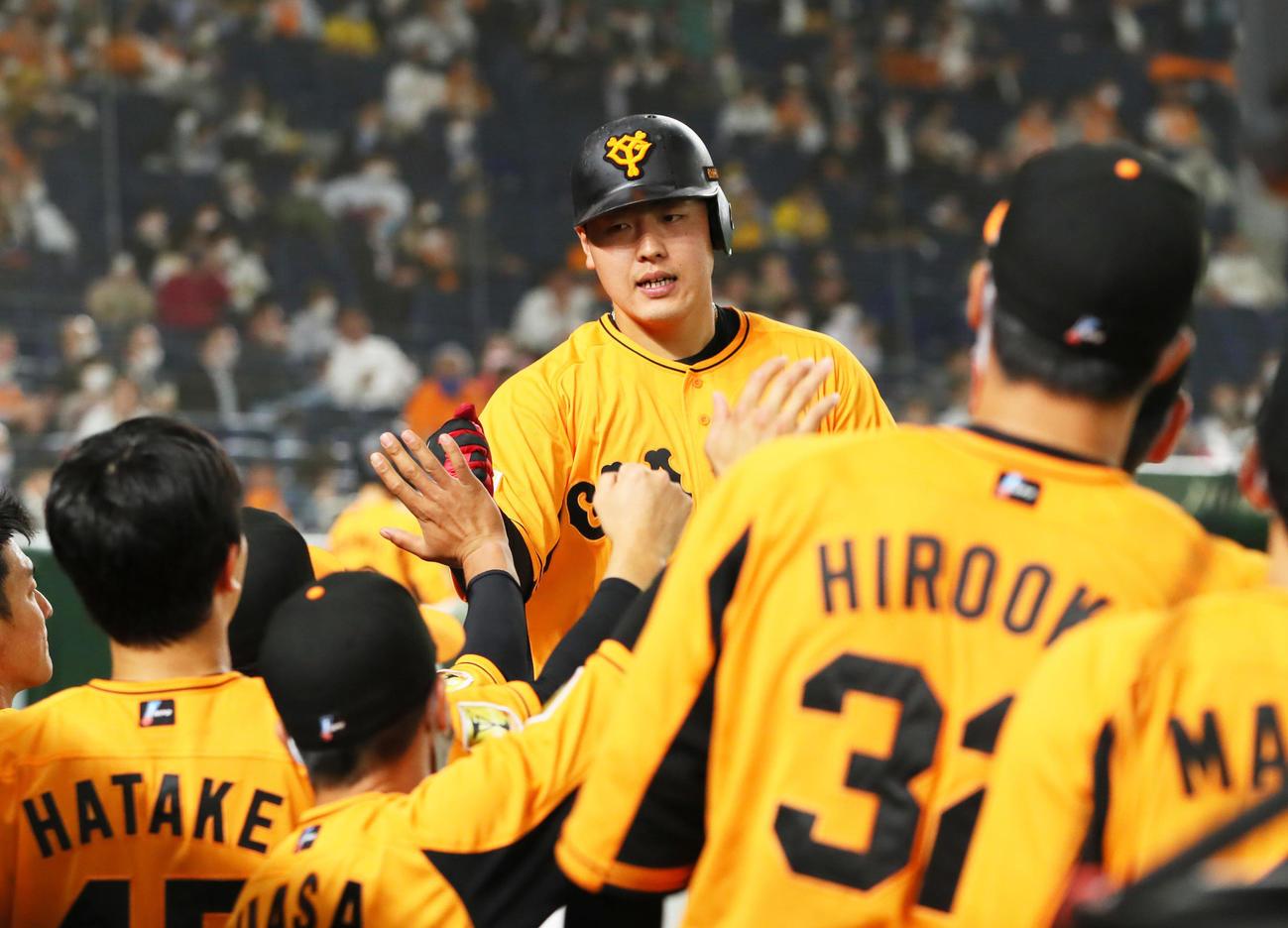 巨人対阪神 4回裏巨人1死、左中間への本塁打を放ちタッチを交わす岡本和(撮影・足立雅史)