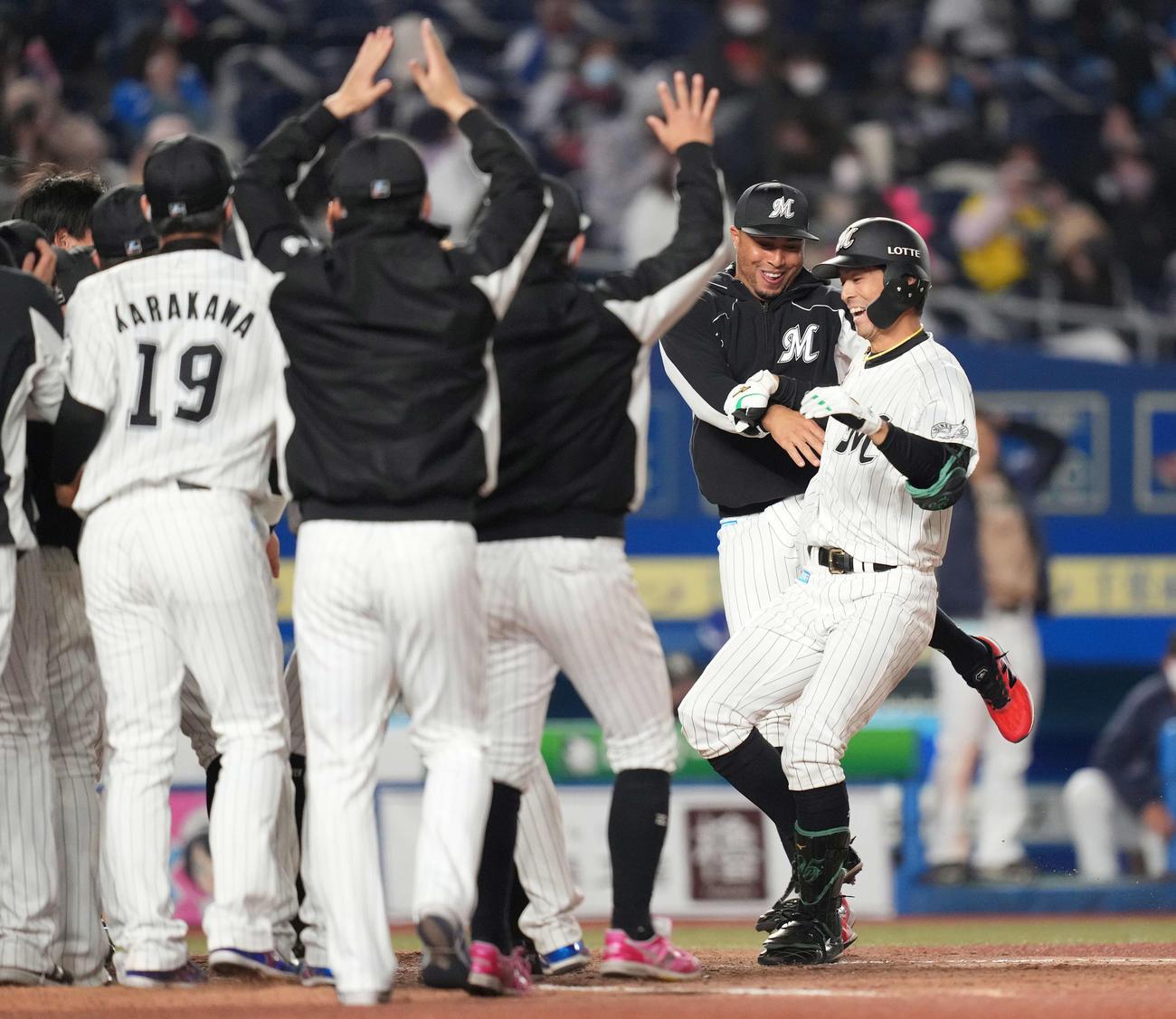 ロッテ対日本ハム 9回裏ロッテ2死一塁、サヨナラの中越え2点本塁打を放った岡(右)はナインの歓喜の輪に飛び込む(撮影・鈴木みどり)